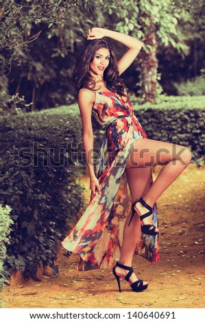 Portrait of a beautiful young woman, model of fashion, in a garden