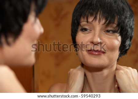Portrait of a beautiful young woman near mirror - stock photo