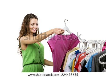 Portrait of a beautiful young woman near rack with hangers deciding what to wear