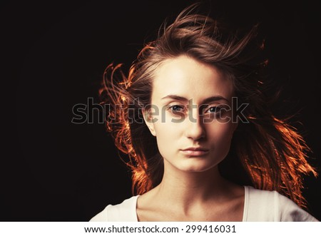 Portrait of a beautiful young woman on a dark background with copy-space. Intentional color shift