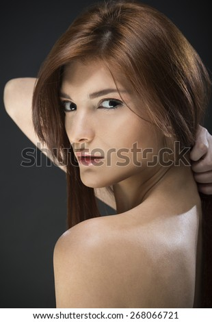 Portrait of a beautiful young woman on black background - stock photo