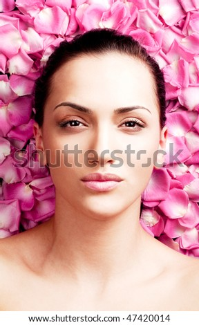 portrait of a beautiful young woman on pink rose petals - stock photo