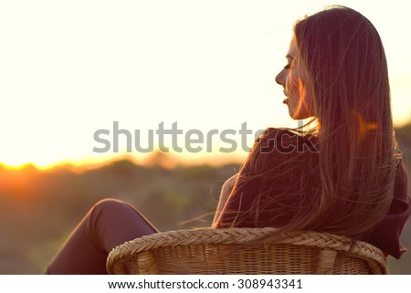Portrait of a beautiful young woman or girl  watching the sunset enjoying nature summer evening outdoors. Soft red light. Sunshine. - stock photo