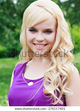 Portrait of a beautiful young woman outdoors - stock photo