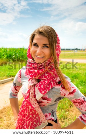 Portrait of a beautiful young woman outdoors. Enjoy nature. Healthy smiling girl in the fields, wearing a scarf in bright summer sun. - stock photo