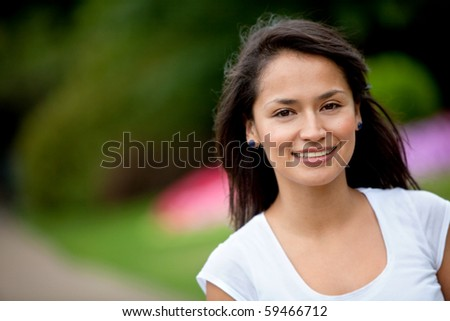 Portrait of a beautiful young woman outdoors smiling - stock photo