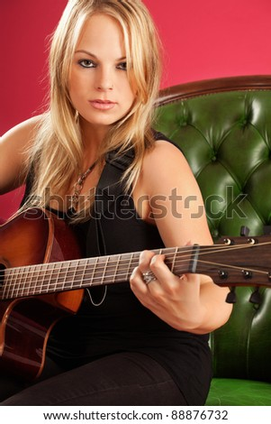 Portrait of a beautiful young woman playing guitar over red background.