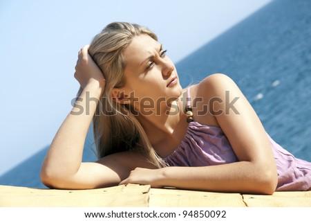 Portrait of a beautiful young woman posing near sea - stock photo