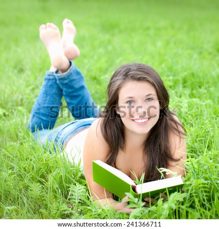 Portrait of a beautiful young woman reading a book, outdoor photo taken in summer - stock photo