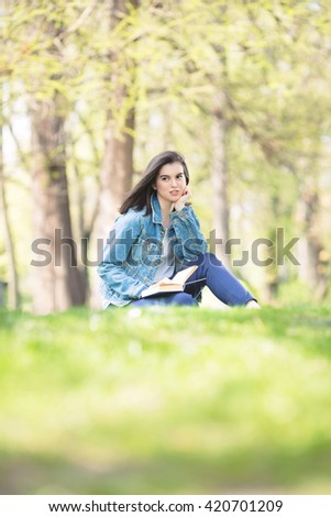 Portrait of a beautiful young woman reading a book. She is sitting on a grass in a park on a nice sunny spring day and thinking while wind is playing with her hair. - stock photo