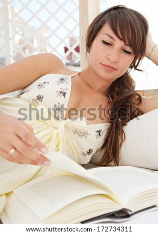 Portrait of a beautiful young woman relaxing and laying down on an exterior bed on a home terrace and reading a book while on holiday in a sunny summer city. Home exterior lifestyle. - stock photo