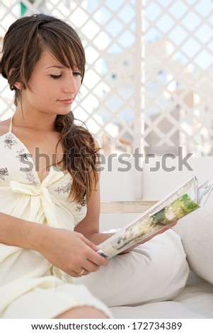 Portrait of a beautiful young woman relaxing and laying down on an exterior bed on a home terrace garden and reading a magazines while on holiday in a sunny summer city. Home exterior lifestyle. - stock photo