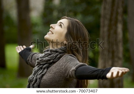 Portrait of a beautiful young woman relaxing with arms open and enjoying the nature - stock photo