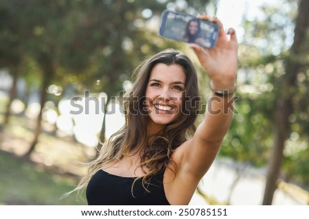 Portrait of a beautiful young woman selfie in the park with a smartphone - stock photo