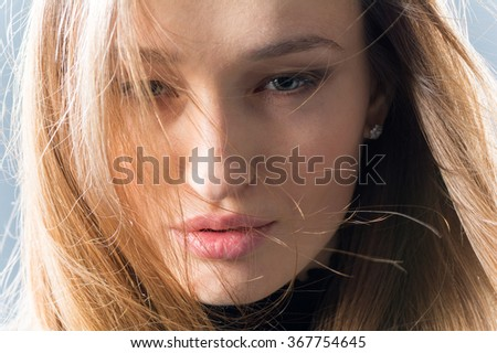Portrait of a beautiful young woman. She looks into the camera. Studio, close-up. - stock photo