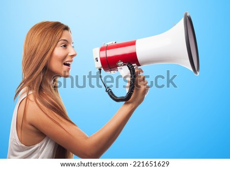 portrait of a beautiful young woman shouting through megaphone - stock photo