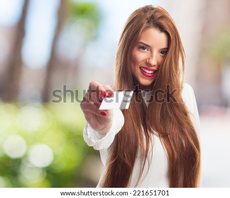 portrait of a beautiful young woman showing a credit card - stock photo