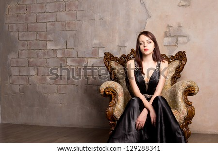 Portrait of a beautiful young woman sitting in a stylish evening gown on an ornate antique wooden armchair against an interior grunge stone wall with copyspace