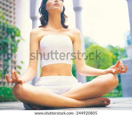 Portrait of a beautiful young woman sitting in yoga pose - stock photo