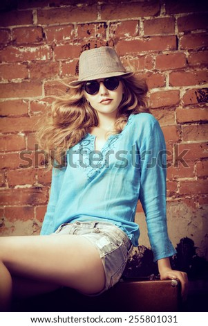 Portrait of a beautiful young woman sitting on her old suitcase near the brickwall. Fashion shot. - stock photo