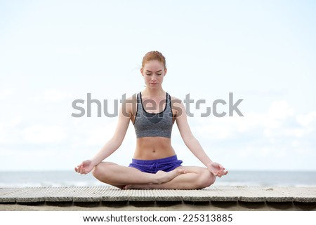 Portrait of a beautiful young woman sitting outdoors in yoga position - stock photo