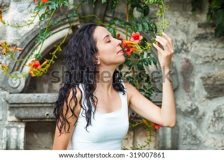 Portrait of a beautiful young woman smelling flowers - stock photo