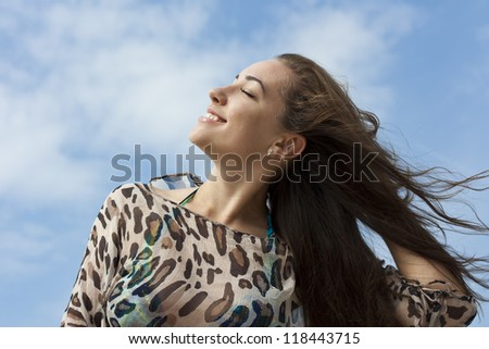 Portrait of a beautiful young woman smiling against the sky. Outdoor - stock photo