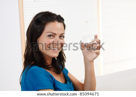 Portrait  of a beautiful young woman smiling and looking at the camera while showing a glass of water.