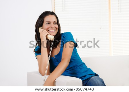 Portrait  of a beautiful young woman  smiling and talking on the phone.