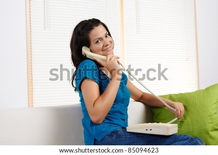 Portrait  of a beautiful young woman  smiling at the camera  while talking on the phone.