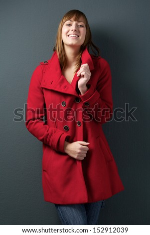 Portrait of a beautiful young woman smiling in red winter jacket - stock photo