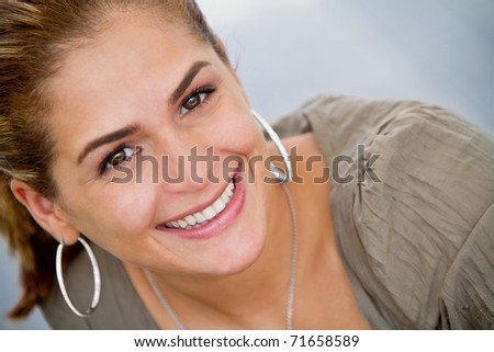 Portrait of a beautiful young woman smiling outdoors - stock photo