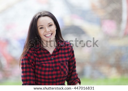 Portrait of a beautiful young woman smiling outdoors, shallow depth of field - stock photo