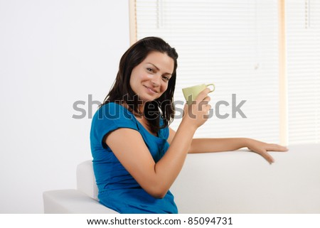 Portrait  of a beautiful young woman smiling while lifting  a cup of coffee. - stock photo