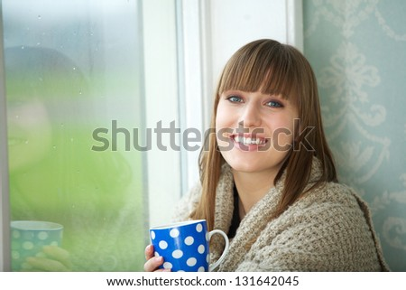 Portrait of a beautiful young woman smiling with cup of tea - stock photo