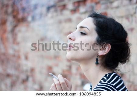 Portrait of a beautiful young woman smoking - stock photo