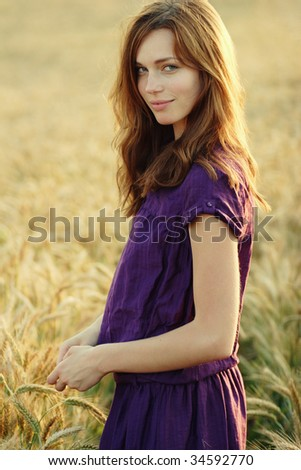 portrait of a beautiful young woman standing in a field of wheat - stock photo