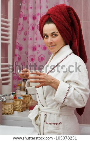 Portrait of a beautiful young woman standing in her bathroom in a robe, with towel on head, preparing to brush her teeth, smiling into camera - stock photo