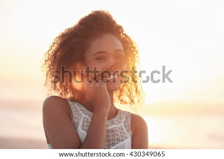 Portrait of a beautiful young woman standing on a beach at sunset - stock photo