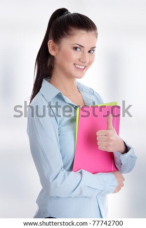 Portrait of a beautiful young woman student gesturing. - stock photo