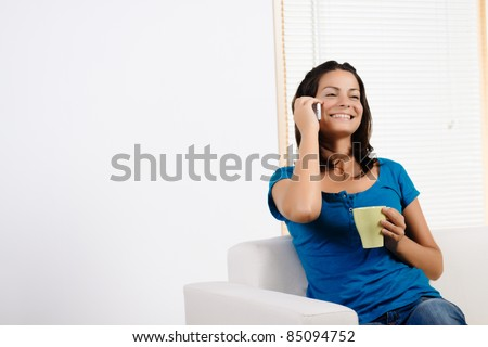Portrait  of a beautiful young woman talking on a mobile phone and laughing.