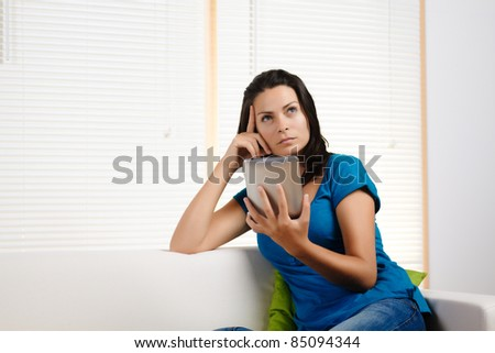 Portrait  of a beautiful young woman thinking while holding  a tablet PC. - stock photo