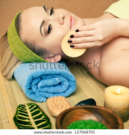Portrait of a beautiful young woman touching her face with a special sponge at a spa salon. Perfect Skin. Skincare. Young Skin - stock photo