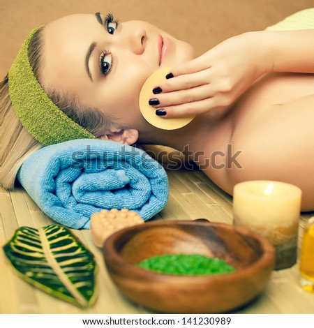 Portrait of a beautiful young woman touching her face with a special sponge at a spa salon. Perfect young skin and hair. Skincare and haircare. Close up. Indoor shot - stock photo