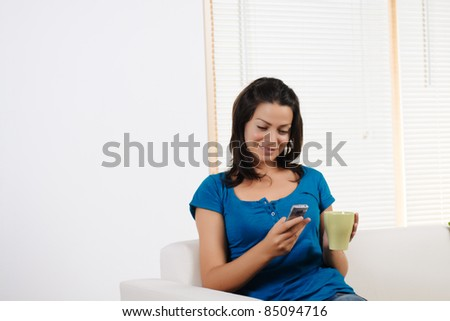 Portrait  of a beautiful young woman using a mobile phone with a  cup of coffee. - stock photo
