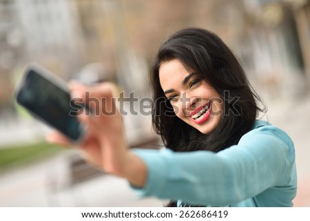Portrait of a beautiful young woman, using braces, selfie in the street with a smartphone - stock photo