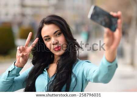 Portrait of a beautiful young woman, using braces, selfie in the street with a smartphone doing v sign