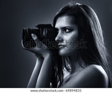 Portrait of a beautiful young woman using dslr camera