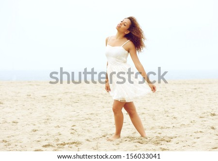 Portrait of a beautiful young woman walking on beach in white dress - stock photo