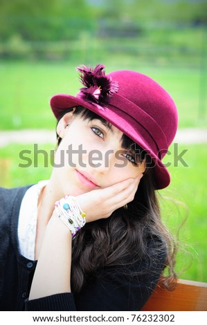 Portrait of a beautiful young woman wearing a retro hat, daydreaming - stock photo